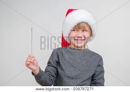 New horisontal emotional portrait of caucasian boy with santa claus red hat