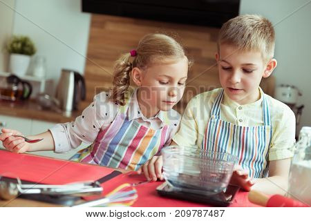 Portrait Of Two Happy Children Having Fun During Cooking Christmas Cookies At Kitchen
