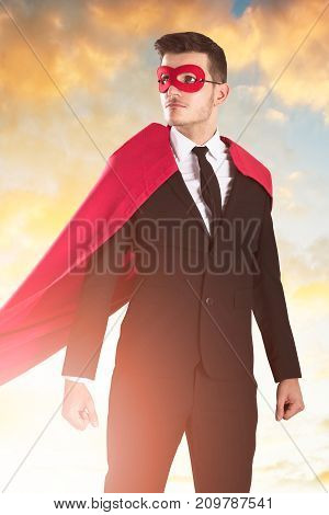 Portrait Of Young Businessman In Superhero Costume Against Dramatic Sky