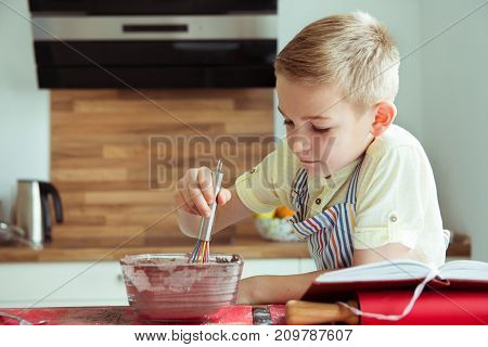 Portrait Of Young Boy Preparing Chocolate Cookies At Kitchen