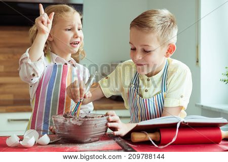 Portrait Of Two Happy Children Which Having Fun During Cooking Christmas Cookies