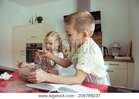 Two Happy Children Baking Christmas Cookies At Kitchen