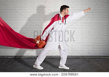 Superhero Doctor In Red Cape Carrying First Aid Box Before Flying