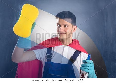 Young Happy Male Janitor In Red Cape Cleaning Glass