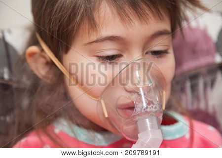 Little girl is wearing a breathing mask and playing games on mobile phoneShe is sick. Girl is inhaling medicine through inhaler at home. She dressed in dotted pink pajamas. Her disease is pneumonia. Little girl is wearing a breathing mask and playing gam