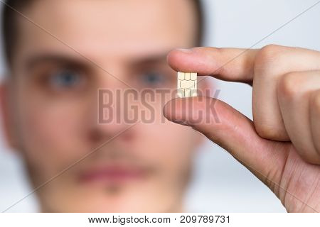 Close-up Of A Man Holding Nano Sim Card Between Fingers