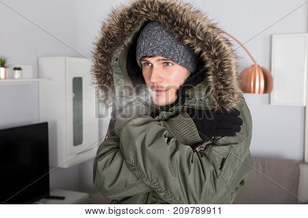 Young Man With Warm Clothing Feeling The Cold Inside House