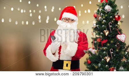 holidays, technology and people concept - man in costume of santa claus and christmas tree dialing number on smartphone