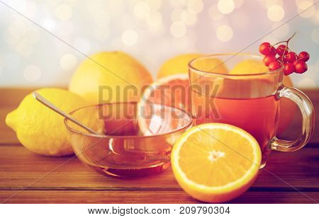 health, traditional medicine, folk remedy and ethnoscience concept - cup of tea with honey, lemon and rowanberry on wooden background