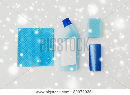 cleaning stuff, housekeeping and household concept - bottle of detergent or toilet cleaner, blue rag, sponge and rubbish bags on white background over snow