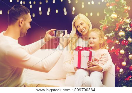 christmas, holidays, family and people concept - father photographing happy mother and little daughter with present by smartphone over lights background