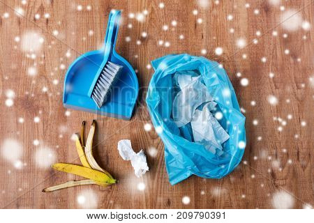 housework, housekeeping, household, waste and garbage cleaning concept - close up of rubbish bag with trash and dustpan on wooden floor over snow