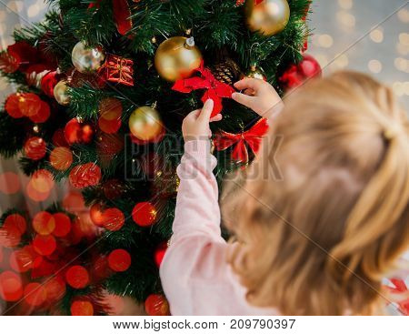 new year, holidays and people concept - close up of little girl decorating christmas tree at home