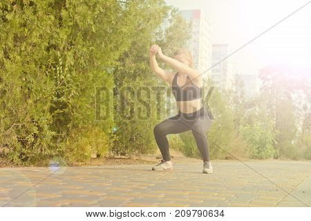 A girl is doing a warm-up before jogging against the background of high-rise buildings
