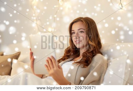 technology, internet, christmas and people concept - happy young woman lying in bed with tablet pc computer at home bedroom over snow