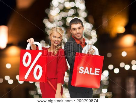 sale, holidays and people concept - happy couple with discount sign on shopping bags over christmas tree lights background