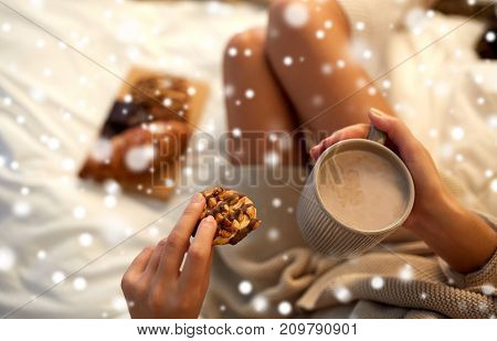 winter, leisure and people concept - close up of young woman with cup of coffee or cacao and cookie in bed at home over snow