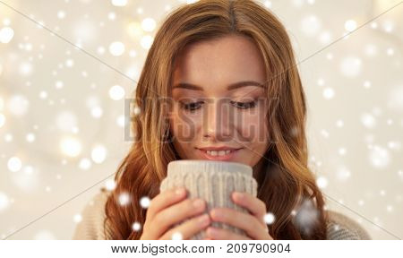 christmas, winter and people concept - close up of happy young woman with cup of coffee or tea at home over snow