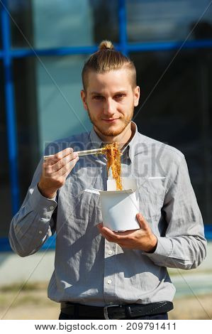 Hansome man eats delicious Chinese egg noodles with vegetables, soy sauce and chili peppers outdoors. Panoramic window on the background. Food concept.