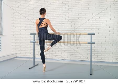 Ballerina stretches herself near barre at ballet studio, full length portrait, shoot from behind