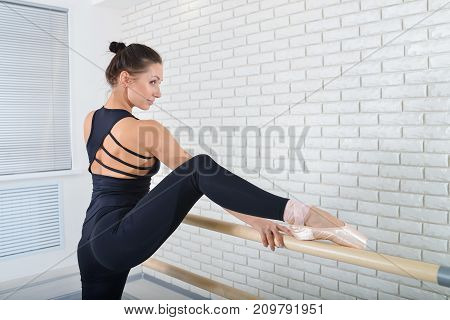 Ballerina stretches herself near barre at ballet studio, three quarter length portrait