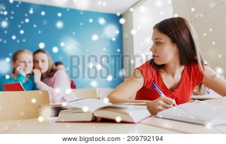 education, bullying, social relations and people concept - students gossiping behind classmate back at school over snow