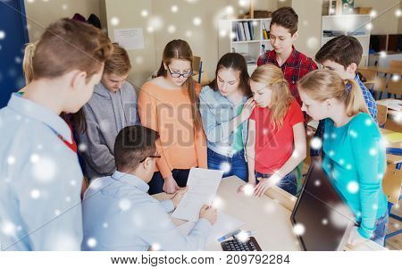 education, learning, teaching and people concept - group of students and teacher checking tests at school over snow