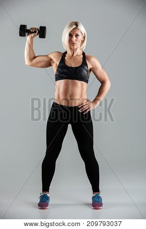 Full length portrait of a focused muscular sportswoman doing exercises with a heavy dumbbell isolated over gray background