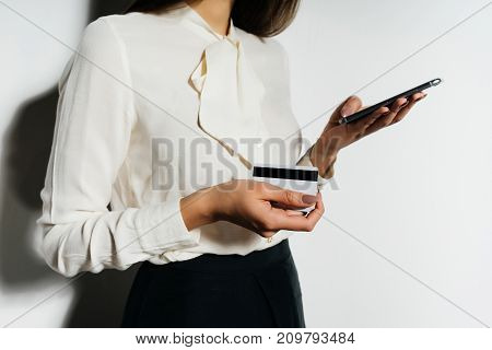 a girl in a business suit looks at her phone