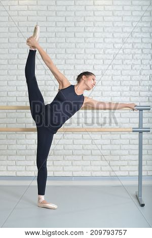 Ballerina stretches herself near barre at ballet studio, full length portrait, performing twine