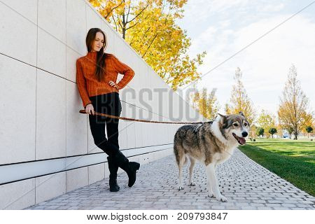 the girl is walking her dog along the park paths