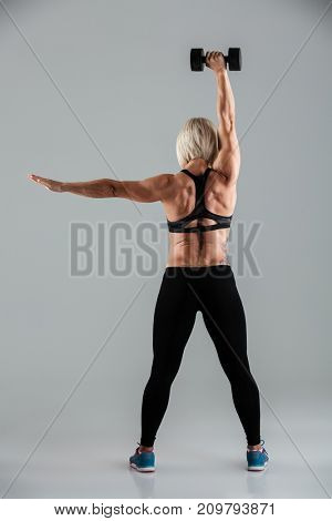 Full length back view portrait of a fit sportswoman doing exercises with a heavy dumbbell isolated over gray background