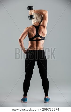 Full length back view portrait of a muscular fit sportswoman doing exercises with a heavy dumbbell isolated over gray background