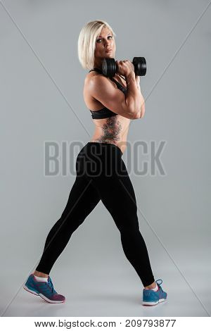 Full length portrait of a confident muscular sportswoman doing exercises with a heavy dumbbell while standing and looking at camera isolated over gray background