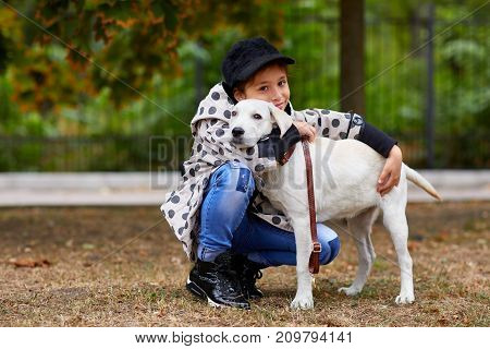 Cute girl kid with doggie walking in the park. Having fun together outdoors on the nature background. Animal concept.