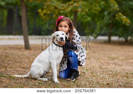 Cute girl kid with doggie walking and hugging in the park. Having fun together outdoors on the nature background. Animal concept.