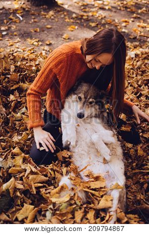 girl is resting in an autumn park with her dog