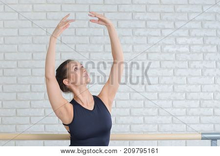Ballerina practicing dance at ballet studio near barre, closeup portrait