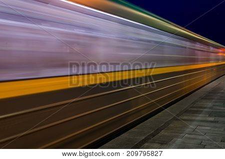 blurred motion of the night blue-yellow train