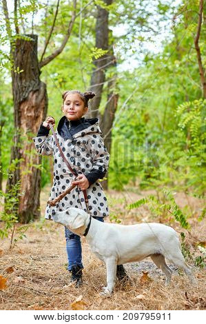 Cute girl with doggie walking and playing in the park. Posing on the camera on the nature background. Full length of girl. Animal concept.