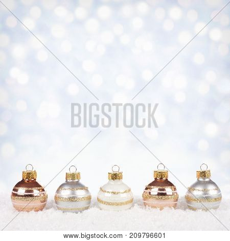 White silver and gold Christmas ornaments in snow with twinkling gold background poster