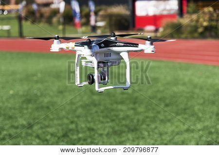 A drone is taking off from a green turf field carrying a camera