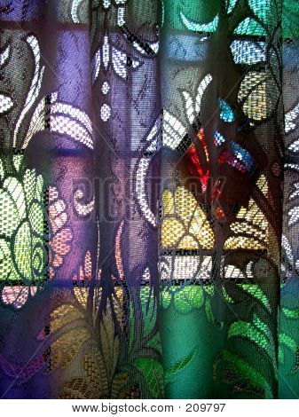 light through a window with a stained diamond creates colors on the lace curtain in front of it. poster