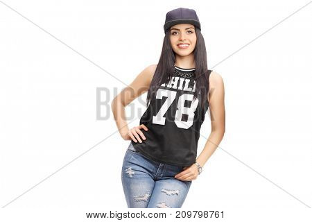 Young woman in a hip-hop outfit leaning against a wall isolated on white background