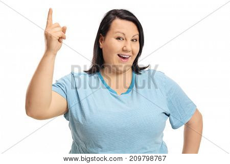 Cheerful young woman pointing up and looking at the camera isolated on white background