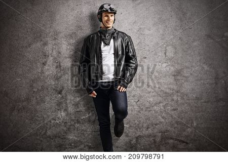 Biker leaning against a rusty gray wall and looking at the camera
