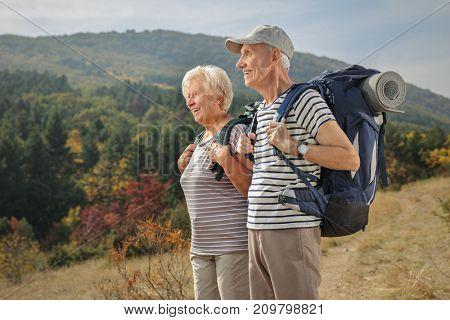 Two elderly hikers looking away outdoors