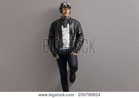 Biker leaning against a gray wall and smiling