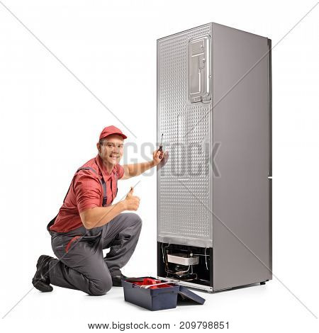 Repairman fixing a refrigerator and making a thumb up sign isolated on white background