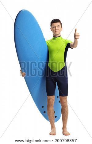 Full length portrait of a teenage surfer with a surfboard making a thumb up gesture isolated on white background